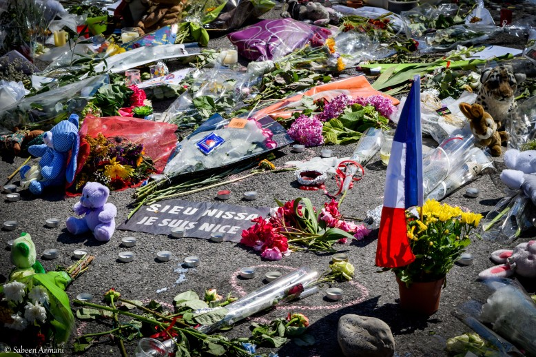 Flowers, plush toys, notes, candles, and flags mark exact spots on the Promenade des Anglais where lives were claimed